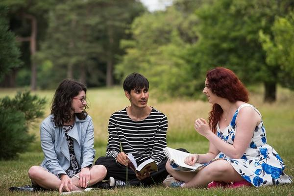 Three students talking outside sat on a grass lawn